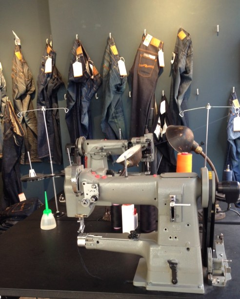 Jeans awaiting repair, and the two sewing machines used to effect repairs