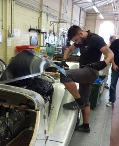 """Sneak photo of a worker """"fettling"""" (aka the art of making things fit) the engine cover to the front wings."""